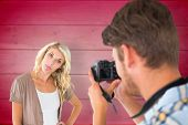 Man taking photo of his girlfriend sticking her tongue out against wooden planks background