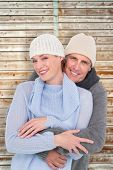Casual couple in warm clothing against wooden background in pale wood