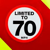 Speed Limited Sign On The Back Of A Vehicle With High Visibility Red And Yellow Chevrons.
