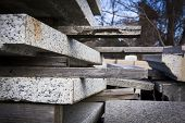 A low angle view of sheets of gray granite stone slabs stacked up with wooden supports on the sides.