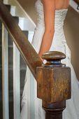 Bride walking up old oak staircase