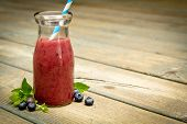Jar containing blueberry smoothie with lined straw and fresh fruits