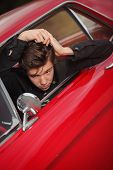 young fashion rocker combing hair in fifties car
