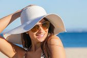 smiling summer woman on beach with sunglasses and floppy hat