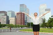 Happy free businesswoman cheering open arms in achievement and success, Japanese city woman carefree in front of Tokyo downtown skyline from the outer imperial palace gardens.