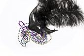 picture of debauchery  - Shiny gold purple blue and silver beads and Mardi Gras mask with feathers on a white background - JPG