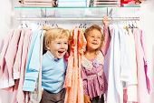 Excited boy and girl play hide-and-seek in store