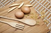 Wooden Utensils, Eggs And Pasta On A Wooden Cutting Board