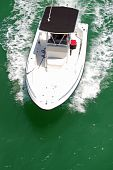 image of outboard engine  - angled overhead view of a small sport fishing boat powered by an outboard engine cruising the florida intercoastal waterway in the vicinity of the southbeach section of Miami Beach - JPG