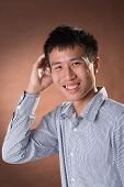Young Chinese frank businessman with shy expression, closeup portrait in studio.