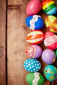 Two rows of painted eggs on wooden background