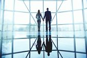 foto of office romance  - Young man and woman in formalwear holding by hands while standing by office window - JPG
