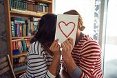 pic of flirty  - Flirty couple sitting in library behind paper with red heart - JPG