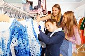 Children and their mother search clothes in store