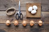 Different eggs, linen napkin, scissors and threads on wooden background