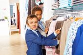 Two boys search clothes while shopping