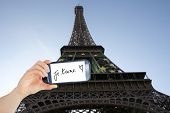Composite image of hand holding smartphone showing je taime against eifell tower