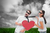 Brunette pulling her boyfriend by the tie holding heart against green grass under grey sky