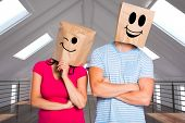 Young couple with bags over heads against white room with skylights