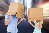 Couple wearing emoticon face boxes on their heads against blurry new york street