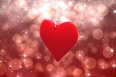 Red heart against shimmering light design on red