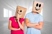 Young couple with bags over heads against bright room with opened windows