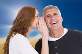 Woman telling secret to her partner against sunny brown landscape