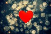 heart against shimmering light design on black