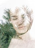 Double exposure portrait of attractive woman combined with photograph of fir branches