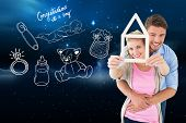Young couple hugging and holding house outline against stars twinkling in night sky