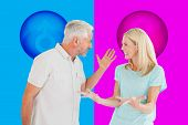 Unhappy couple having an argument against pink and blue