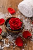 Red rose in bowl with pile of salt ,stones , towel on old wooden board