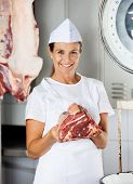 Portrait of confident female butcher holding fresh meat in butchery