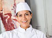 Closeup portrait of confident female butcher smiling in shop