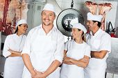 Portrait of happy mature male butcher with team in butchery