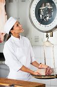 Happy female butcher weighing meat on scale at butchery