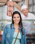 Portrait of beautiful mature woman with butcher in background at butchery