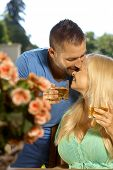 stock photo of cleavage  - Portrait of romantic young couple kissing with drinks in hand - JPG