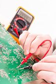 stock photo of multimeter  - Serviceman checks PCB with a digital multimeter in the service workshop - JPG