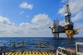 stock photo of rig  - Offshore Jack Up Drilling Rig Over The Production Platform in The Middle of The Sea - JPG
