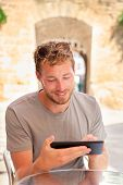 Man using tablet 4g app working in outdoor summer cafe. Young caucasian male adult writing on tablet or reading travel guide e book online during holidays.