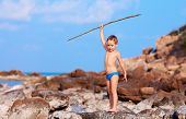 Cute Boy With Bamboo Spear Pretends Like He Is Aborigine On Desert Island