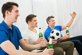 picture of excite  - Three Excited Friends Sitting On Couch Holding Beer Bottles