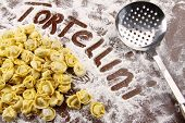 Fresh tortellini and utensil with flour on wooden table