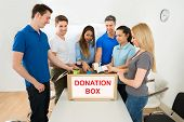 pic of tin man  - Group Of Happy Multiethnic People Putting Cans In Donation Box - JPG