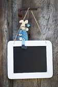 Blue wooden easter bunny sitting on a blackboard and makes advertising.