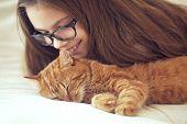 picture of lovable  - Cute ginger cat sleeps near kid girl on the sofa - JPG