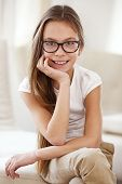Portrait of 8 years old school girl wearing glasses looking at camera