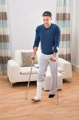 foto of crutch  - Portrait Of A Disabled Man Using Crutches For Walking At Home - JPG