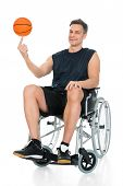 foto of disability  - Disabled Basketball Player On Wheelchair Spinning Ball On His Finger Over White Background - JPG